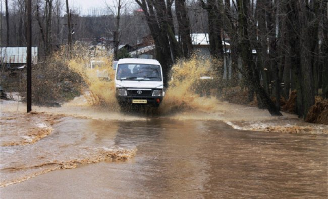 A vehicle moves through a flooded road in Koil village in South Kashmirs Pulwama district ...
