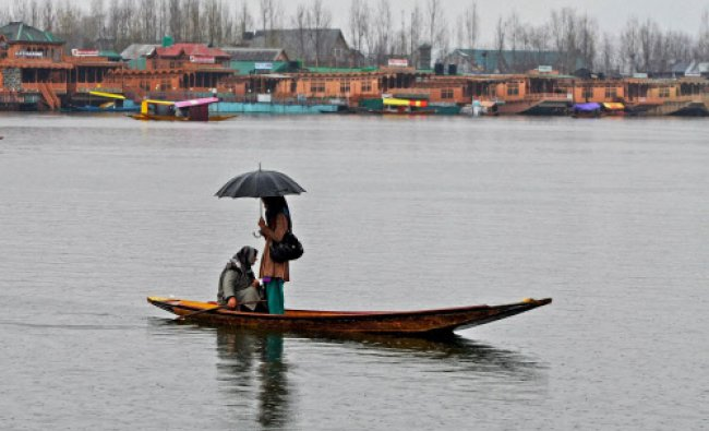 A woman along with her daughter rowing a \'shikara\' at Dal Lake during rains in Srinagar on Tuesday.