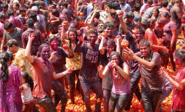 People celebrating \'tomato Holi\' in Surat on Monday. PTI Photo