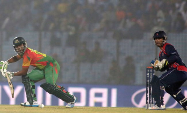 Bangladesh\'s Tamim Iqbal, left, plays a shot as Nepal\'s wicketkeeper Subash Khakurel watches...