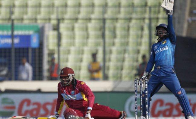 West Indies Chris Gayle falls on ground as Sri Lanka\'s wicketkeeper Kumar Sangakkara appeals...