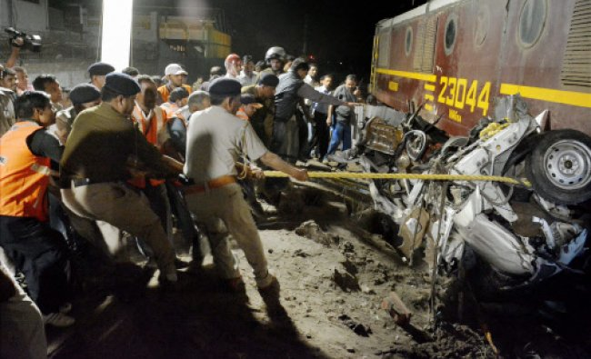 Police and rescue men trying to pull out the wreckage of a car that was crushed by a train...