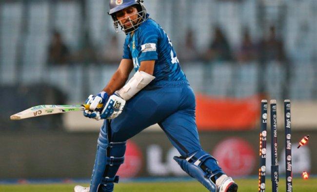Sri Lanka\'s batsman Tillakaratne Dilshan looks back at fallen bails after he is bowled out ...