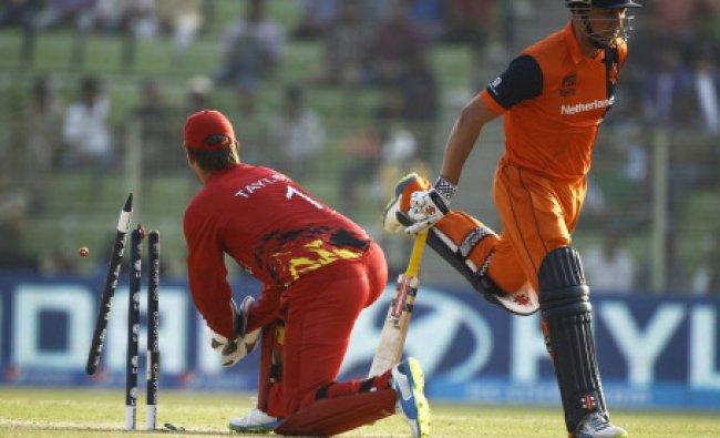 Zimbabwe\'s captain Brendan Taylor, left, dislodges the bails in an unsuccessful attempt ...
