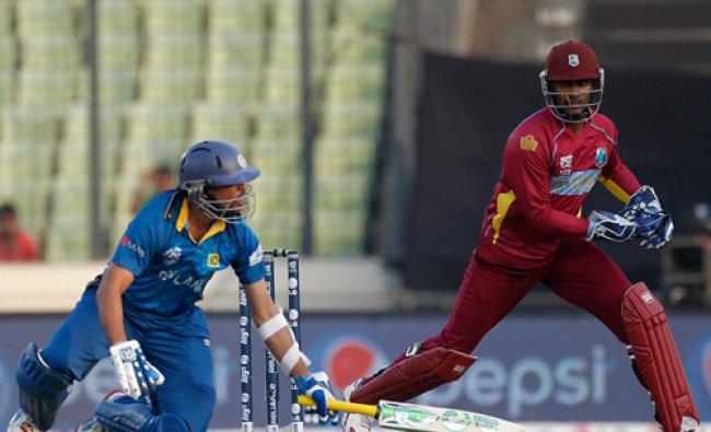 Sri Lanka\'s Tillakaratne Dilshan falls on ground as West Indies wicketkeeper Johnson Charles ...