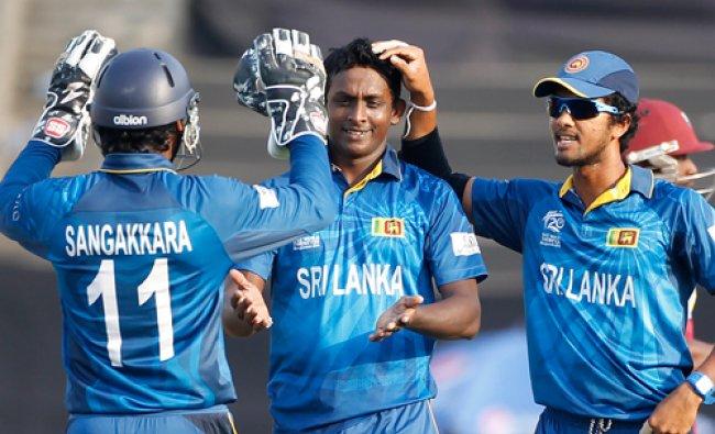 Sri Lanka\'s captain Dinesh Chandimal (R) and Kumar Sangakkara congratulate teammate ...