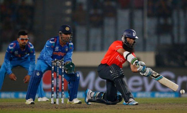 England batsman Moeen Ali, right, plays a shot as India\'s captain Mahendra Singh Dhoni, center...