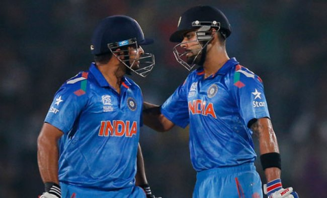 Batsman Virat Kohli, right, pats teammate Suresh Raina on scoring a half century during their ICC...