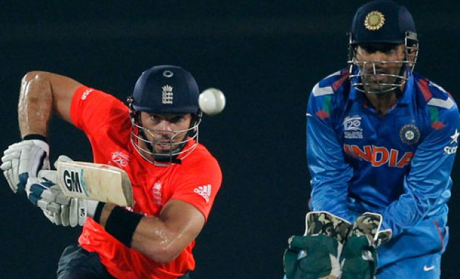England\'s Michael Lumb plays a ball as India\'s captain and wicketkeeper MS Dhoni (R) watches...