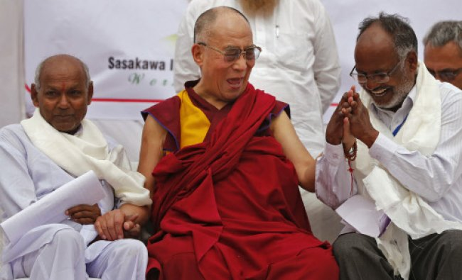 Exiled Tibetan spiritual leader, the Dalai Lama laughs as he holds the hands of leprosy...