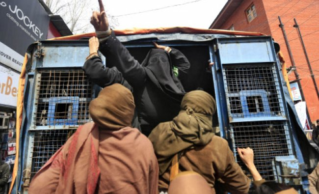 A veil-clad woman activist of Jammu Kashmir Mass Movement (JKMM) shouts slogans from a police van...