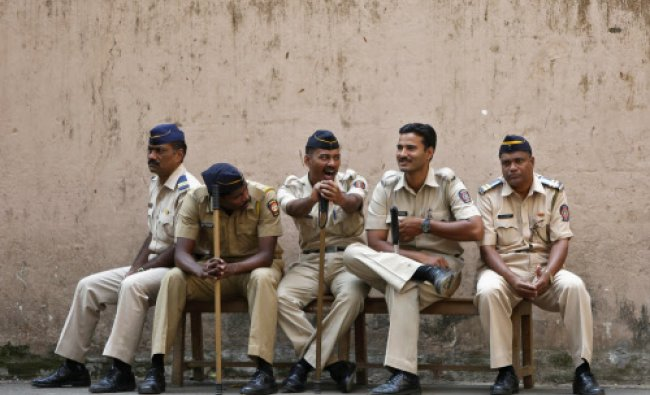 A policeman yawns as he sits with his colleagues outside a court where the case of the gang-rape...