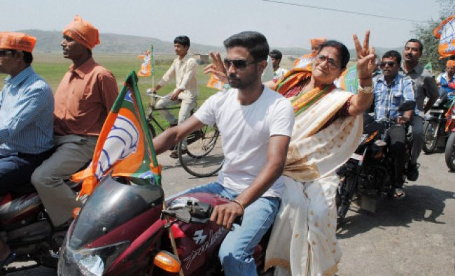 BJP MP Bijoya Chakraborty flashes victory sign from a bike as she takes part in an election...