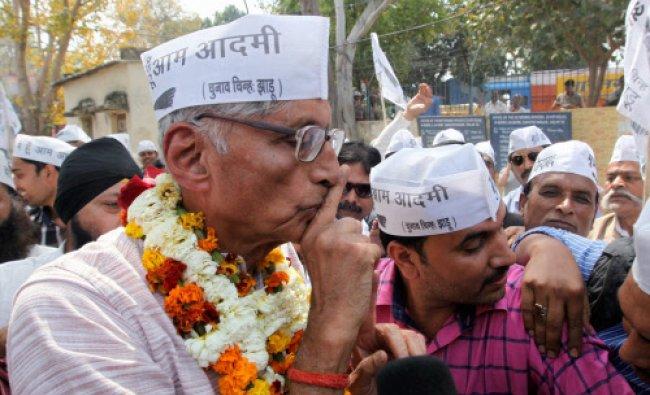 Aam Aadmi Party\'s Delhi East candidate Rajmohan Gandhi gestures as he arrives along with...