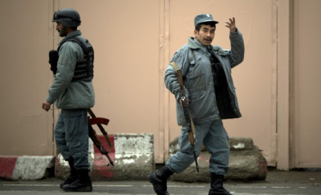 Afghan policemen patrol the entrance to the Serena hotel in downtown Kabul, Friday...