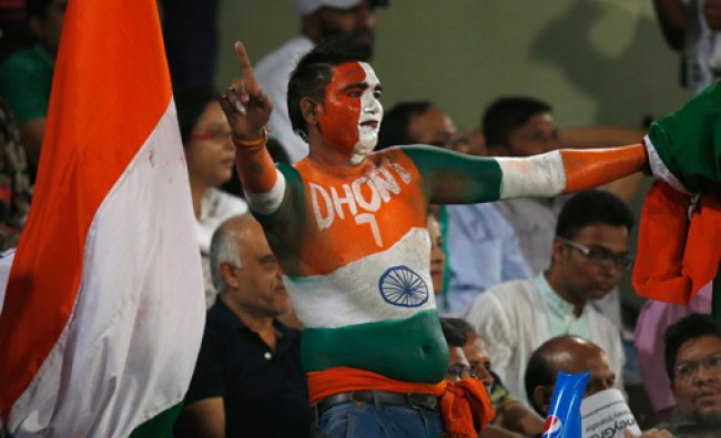 A cricket fan with his body painted in Indian tri-color dances to celebrate a boundary hit by an...