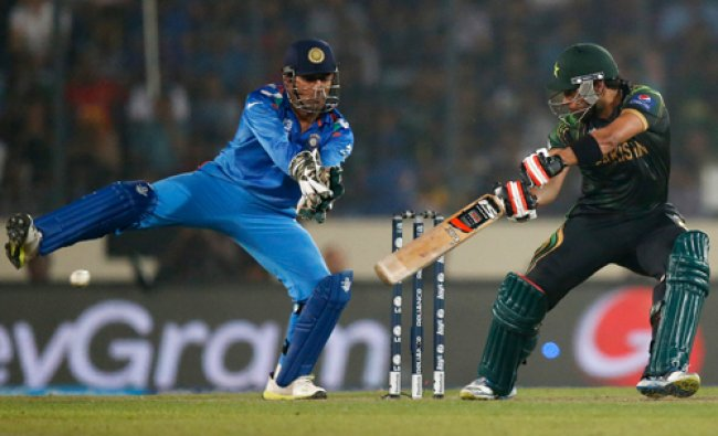Pakistan\'s batsman Umar Akmal, right, plays a shot as India\'s captain Mahendra Singh Dhoni reacts...