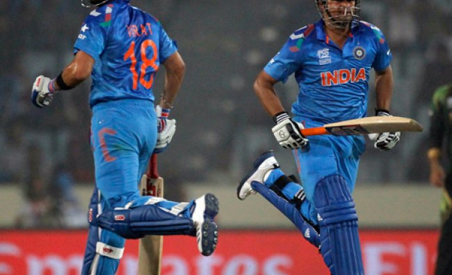 Virat Kohli (L) and Suresh Raina run between the wickets against Pakistan during their match of...