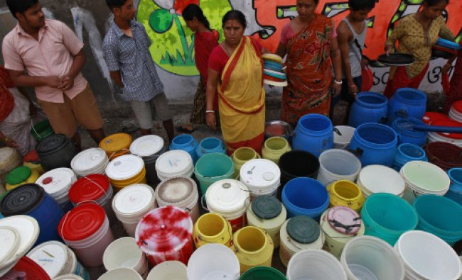 Residents wait to collect free drinking water from a municipal corporation water tanker...