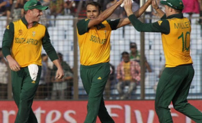 South African cricket player Imran Tahir, second left, celebrates with David Miller and...