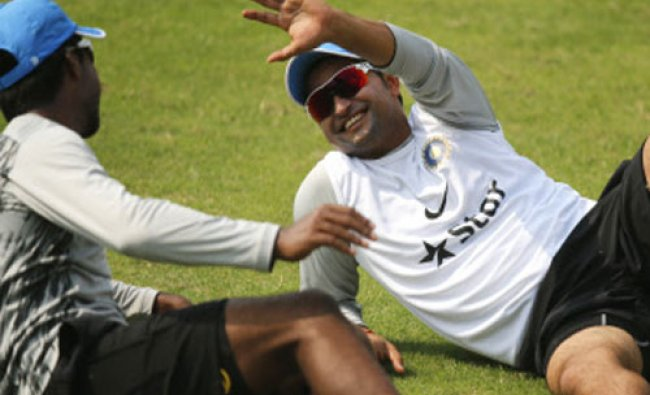 India\'s Suresh Raina, shares a light moment with teammate Varun Aaron during a training session...