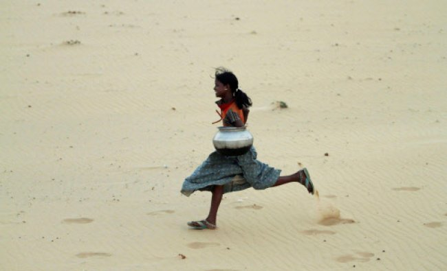 A girl holds an empty vessel and runs to fill water from River Kuakhai on the World Water Day...