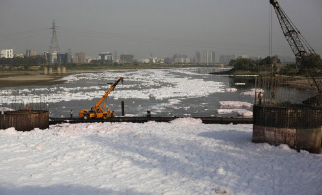 Thick foam from pollution surrounds a bridge under construction over the Yamuna River on world...