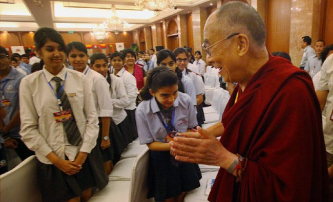 Tibetan spiritual leader the Dalai Lama is greeted by students as he arrives...