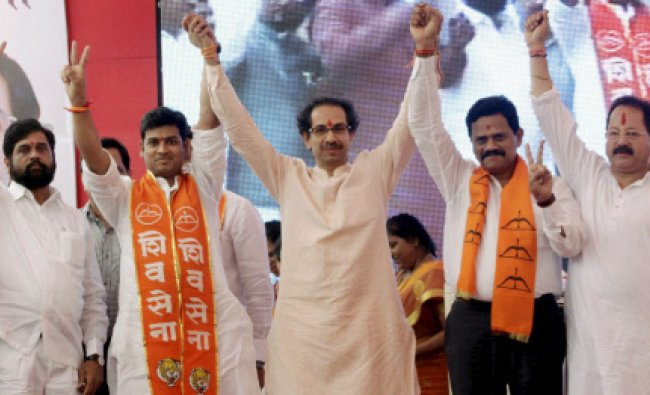 Shiv Sena chief Uddhav Thackeray (centre) raises hands with party candidates...