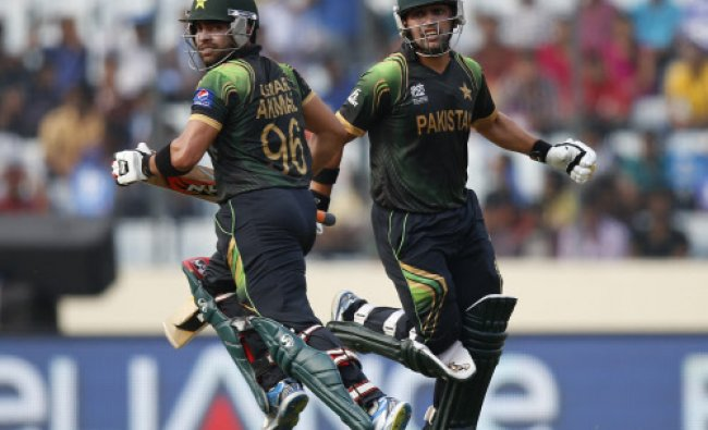 Pakistan\'s batsmen Umar Akmal, left, and Kamran Akmal run between the wickets to add runs...