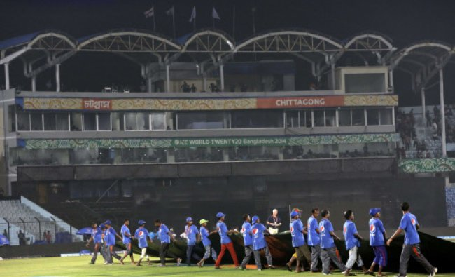 Groundsmen cover the pitch to protect from rain during ICC Twenty20 Cricket World Cup match...