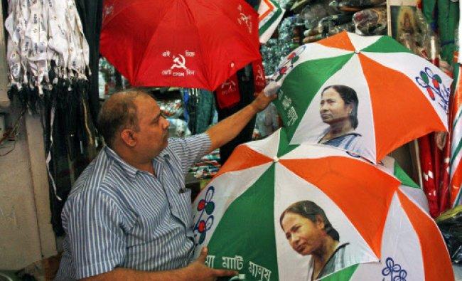 A shopkeeper displays umbrellas with symbols of various political parties at his shop in Kolkata...