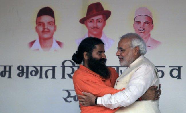 Narendra Modi, right and Indian yoga guru Baba Ramdev, left, greet each other during...