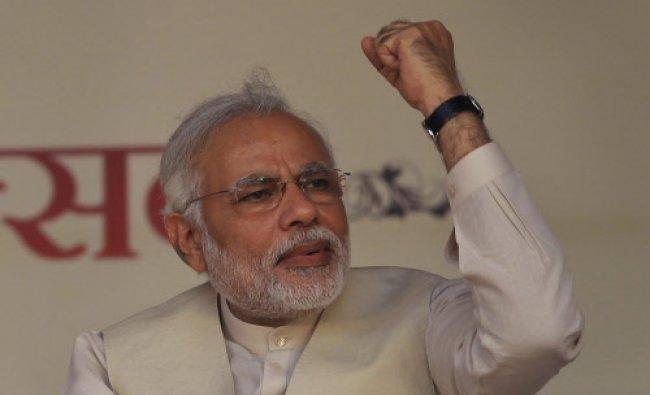 Narendra Modi, raises his hand as others shout patriotic slogans during a yoga festival...