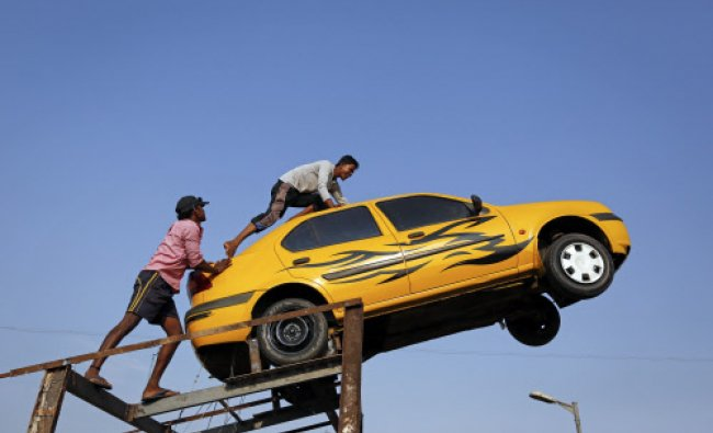 Workers try to dismantle a car which was used for a television show advertisement in Mumbai...
