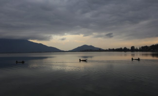 Fishermen row their shikara, or traditional boat, homeward after a day\'s work on the Dal Lake...
