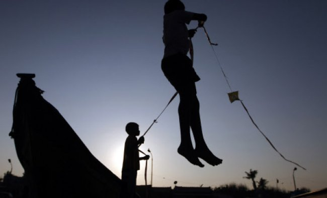 Two boys are silhouetted as they fly a kite on the Marina beach in Chennai...