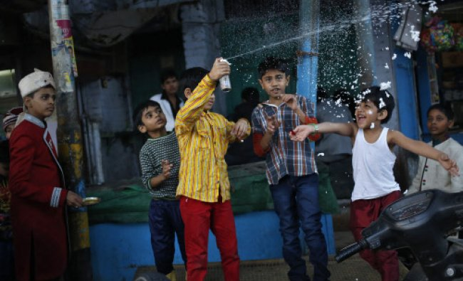 Children play with foam along a roadside in the old quarters of Delhi...