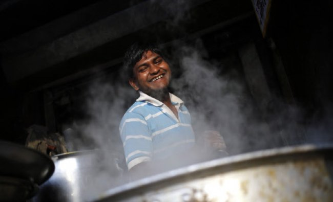 A worker at a food stall smiles as he prepares food at a market in the old quarters of Delhi...