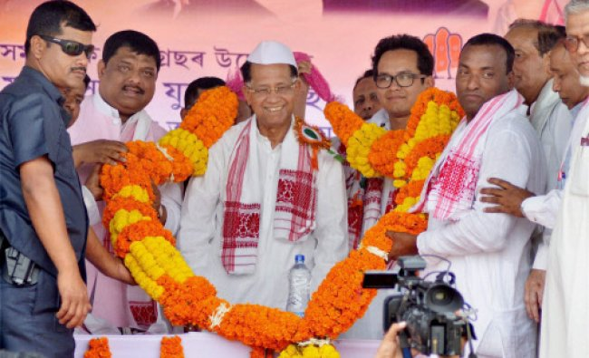 Assam Chief Minister Tarun Gogoi being garlanded by supporters at an election rally...