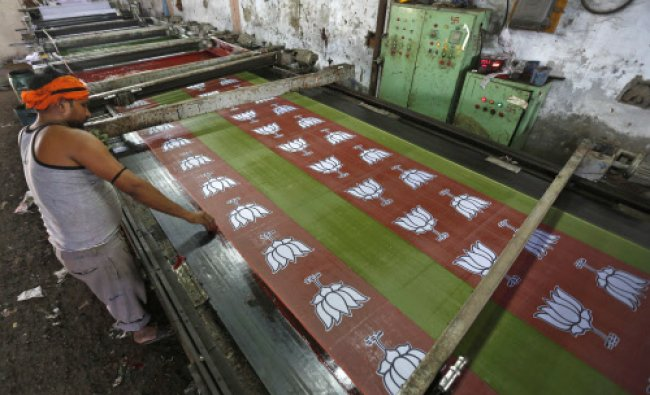 A worker prints the flags of India\'s main opposition Bharatiya Janata party (BJP) inside a flag...