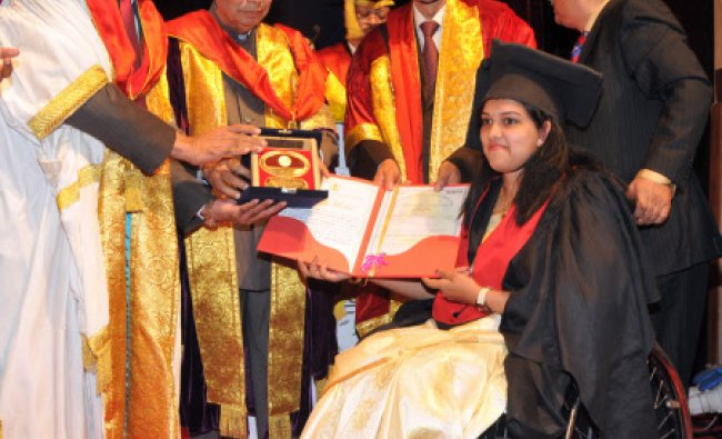 Governor of Karnataka H R Bhardwaj handing over the award to Disabled student Dr S J Rajalakshmi...