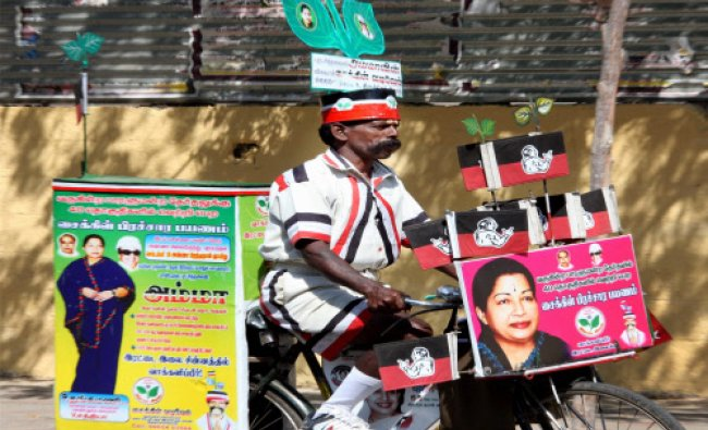 A supporter of AIADMK campaigns on a bicycle decorated with posters in Coimbatore on Wednesday...