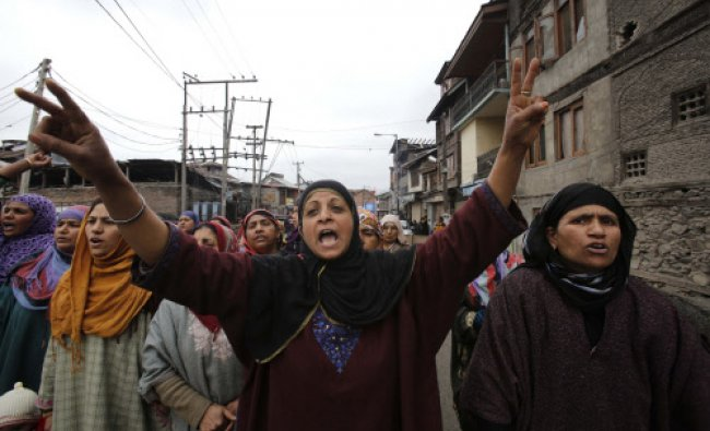Kashmiri women block a road and shout slogans demanding the release of two detained men in ...