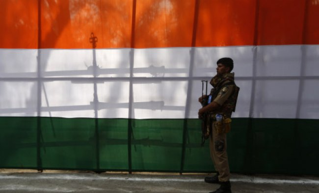 A security officer stands guard during the release of the Congress party\'s election manifesto...