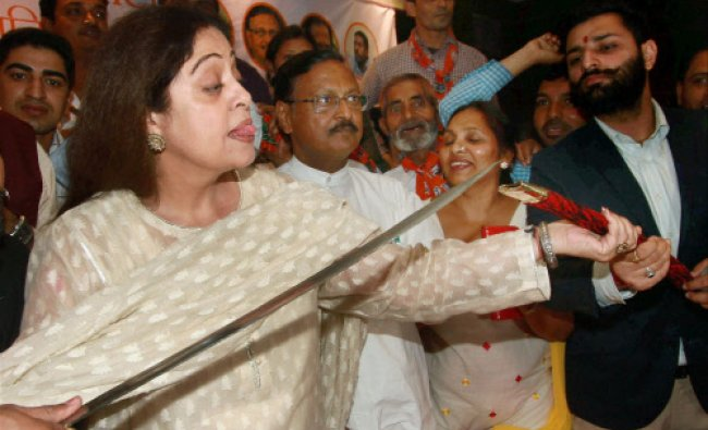 BJP candidate Kirron Kher holds a sword during a meeting in Chandigarh...