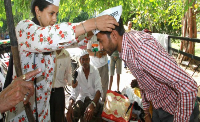 Aam Adami Party candidate Gul Panag offers party cap to a supporter during her election...
