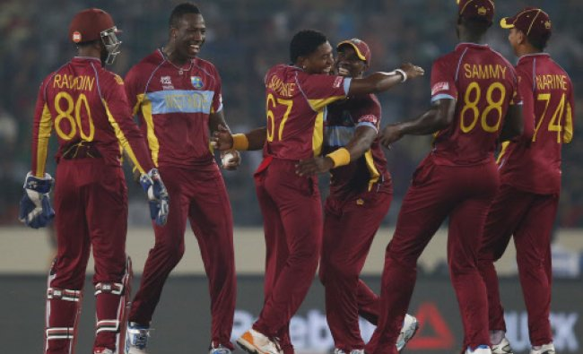 West Indies\' bowler Krishmar Santokie, third left, celebrates with teammates the dismissal...