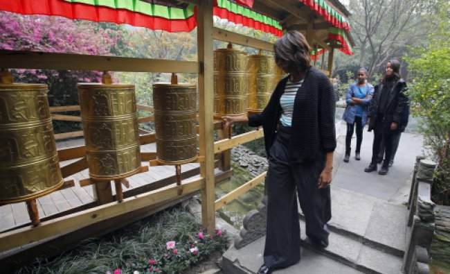 In this March 26, 2014, photo, U.S. first lady Michelle Obama, left, touches Tibetan prayer ...
