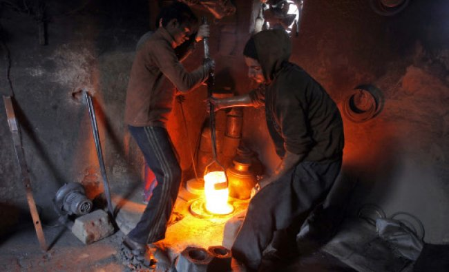 Workers lift a furnace carrying melted copper to make utensils and accessories inside a workshop...
